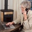 Female Pensioner Using Laptop And Mobile Phone — Stock Photo