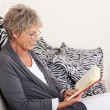 Elderly woman reading a book sitting on the sofa — ストック写真