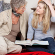 Grandmother and granddaughter reading a book — Stock Photo #27361649