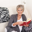 Smiling Senior Woman With Book Sitting On Sofa — Stock Photo