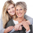 Happy Teenage Girl Embracing Grandmother From Behind — Stock Photo #27361825