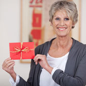 Smiling elderly woman showing a decorated envelope — Stock Photo