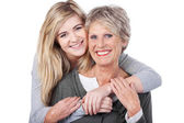 Happy Teenage Girl Embracing Grandmother From Behind — Stock Photo