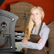 Smiling woman producing roasted coffee beans — Stock Photo