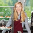 Smiling waitress leaning on coffee shop counter — Stock Photo