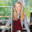 Stock Photo: Smiling waitress leaning on coffee shop counter