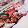 Saleswoman offering fresh meat in supermarket — Stock Photo #27398123