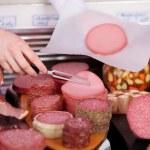 Butchery worker selling sliced salami — Stock Photo