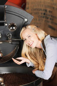 Woman checking quality of coffeebeans — Stock Photo