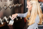 Waitress filling coffee beans in a bag — Stock Photo