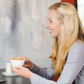 Cheerful blonde woman enjoying cappuccino — Stock Photo