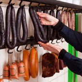 Butcher Arranging Sausages On Hooks — Stock Photo