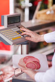 Butcher Holding Cold Cuts While Pressing Button On Weighing Scal — Stock Photo