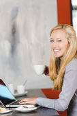 Woman using laptop at cafe — Foto Stock