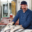 Man selling salmon at fish market — Stock Photo