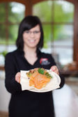 Smiling waitress displaying salmon dish — Stock Photo