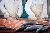 Workers Slicing Fishes At Table — Stock Photo