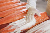 Hand Applying Salt On Sliced Fish On Table — Stock Photo