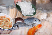 Salesperson filling ice on fresh fish — Stock Photo