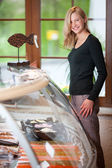 Woman Standing By Display Cabinet At Fish Store — Stock Photo