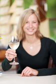 Smiling pretty woman toasting with white wine — Stock Photo