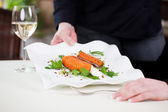Waitress Serving Salmon Dish Garnished With Parsley At Table — Stock Photo