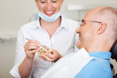 Smiling Female Dentist Explaining Artificial Teeth — Stock Photo