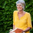 Relaxes senior lady with book in the garden — Stock Photo