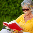 Senior woman looking over sunglasses while reading — Stock Photo
