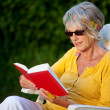 Elderly lady reading a book with sunglasses — Stock Photo #27448023