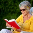 Elderly lady reading a book with sunglasses — Stock Photo