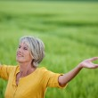 Senior Woman Enjoying Nature On Grassy Field — Stock Photo #27448059