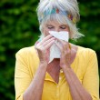 Senior Woman Blowing Nose In Tissue Paper — Stock Photo #27448221
