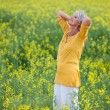 Senior Woman With Hand Behind Head Standing On Field — Stock Photo