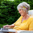 Senior Woman Using Laptop On Chair At Park — Stock Photo