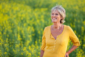 Happy senior woman standing in on field — Stock Photo