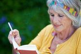Senior vrouw lezen boek terwijl roken sigaretten — Stockfoto