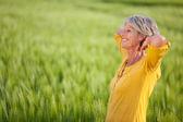 用手在头上绿草如茵的球场上后面的高级女人 — 图库照片
