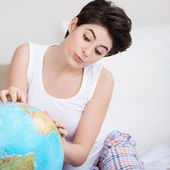 Woman looking for a destination on the globe — Stock Photo