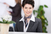 Beautiful female receptionist welcoming with smile — Stock Photo