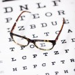 Stock Photo: Glasses lying on eye test chart