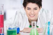 Femme scientifique avec des produits chimiques sur l'avant-plan en laboratoire — Photo