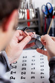 Optician Fixing Lens On Frame At Workshop — Stock Photo
