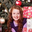 Pretty girl peering around Christmas presents — Foto Stock