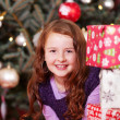 Pretty girl peering around Christmas presents — Stok fotoğraf