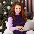 Girl relaxing in front of a Christmas tree — Stock Photo