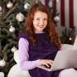 Girl relaxing in front of a Christmas tree — Foto de Stock