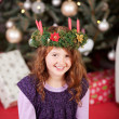 Smiling girl wearing an Xmas candle wreath — Stock Photo
