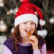 Little girl eating Christmas candy — Stock Photo