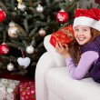 Smiling little girl in front of a Christmas tree — Stok fotoğraf